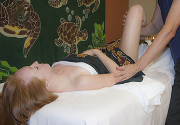 Person getting leg moved by therapist during day spa massage