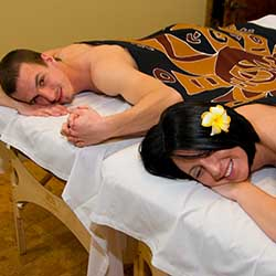 Couple receiving romantic side by side massage in day spa