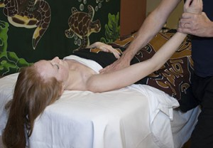 Woman face up getting pectoral muscle massaged