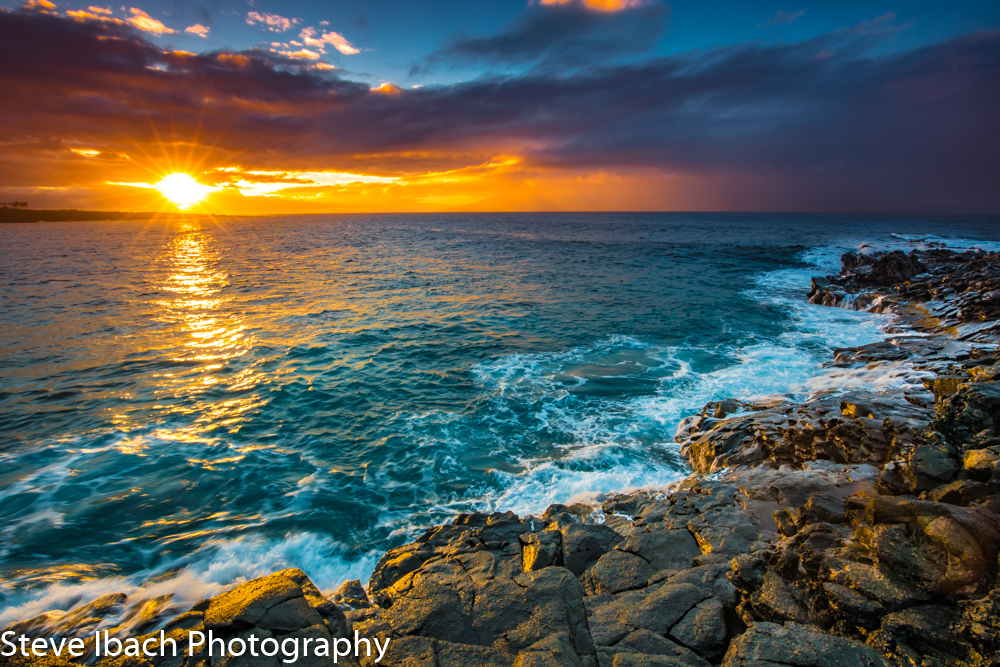 Photograph of sunset from rocky shore in Maui, HI