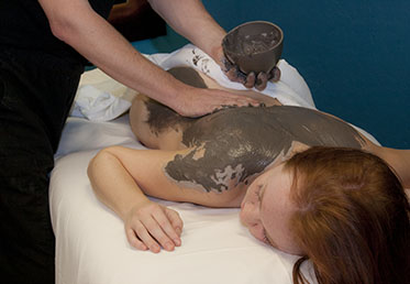 Woman receiving cocoa body wrap in Goodyear, AZ day spa