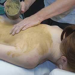 Woman receiving clay body treatment in Chandler, AZ day spa